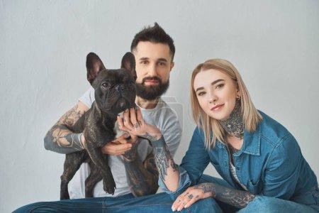 Photo pour Jeune couple tatoué tenant bouledogue français et souriant à la caméra sur fond gris - image libre de droit