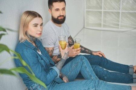 young couple holding glasses of juice and looking away while sitting in floor in new house