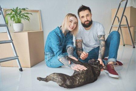 Photo pour Heureux jeune couple joue avec le bouledogue français et souriant à la caméra à nouveau domicile - image libre de droit