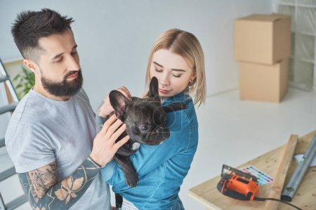 portrait of tattooed couple with french bulldog at new home