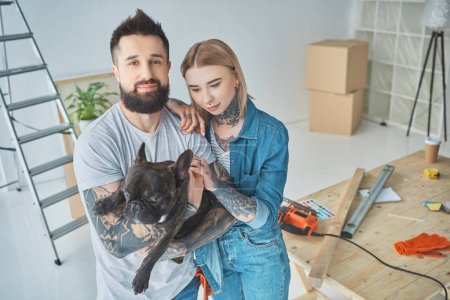 Photo for Tattooed couple with french bulldog at new home - Royalty Free Image