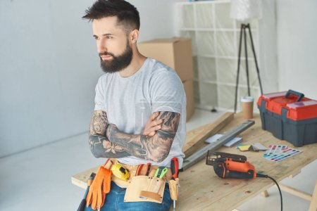 side view of pensive bearded repairman with tattoos and tools leaning on wooden surface in new apartment
