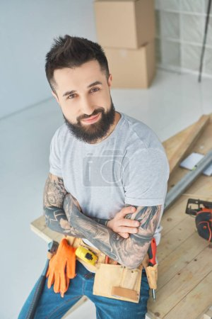 smiling repairman with tattoos and tools leaning on wooden surface in new apartment