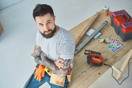 high angle view of bearded repairman with tattoos leaning on wooden table with equipment
