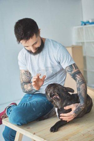 Photo pour Homme tatoué, jouant avec le bouledogue français sur une surface en bois dans appartement neuf - image libre de droit
