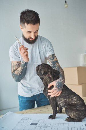 tattooed repairman with pencil and french bulldog standing at blueprint of new apartment on wooden tabletop
