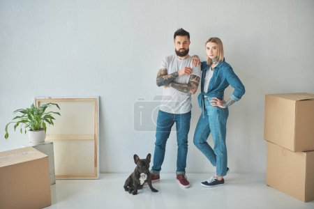 Photo for Young couple standing at new home with cardboard boxes and french bulldog - Royalty Free Image