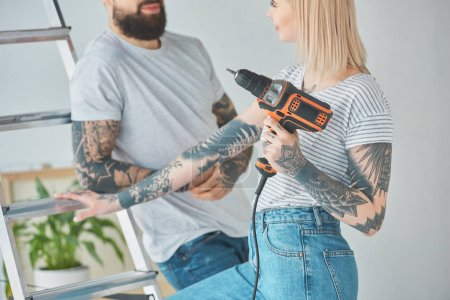 partial view of tattooed couple with screw gun standing at ladder at new home