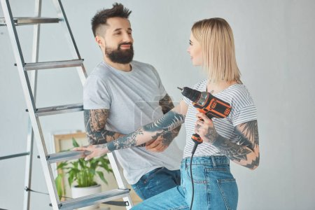 tattooed couple with screw gun standing at ladder at new home