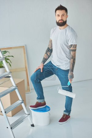 tattooed repairman with roll paint brush standing in new apartment with ladder and plastic bucket of paint