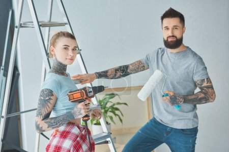 tattooed couple with screw gun and roll paint brush standing at ladder at new home