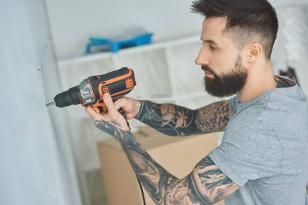 tattooed man doing hole in wall with screw gun in new apartment, inexperienced millennial concept