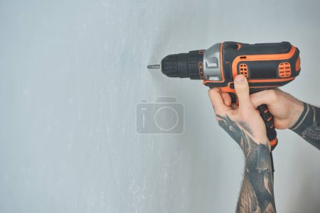 cropped shot of tattooed man doing hole in wall with screw gun in new apartment, inexperienced millennial concept