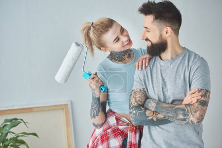 portrait of woman with roll paint brush looking at boyfriend at new home