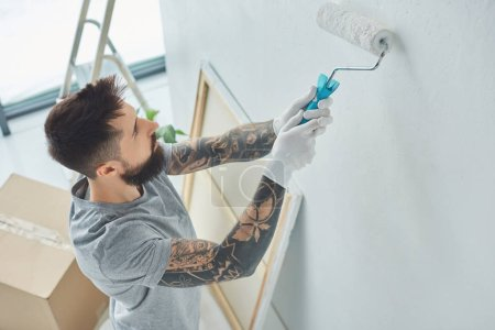side view of tattooed repairman painting wall in new apartment