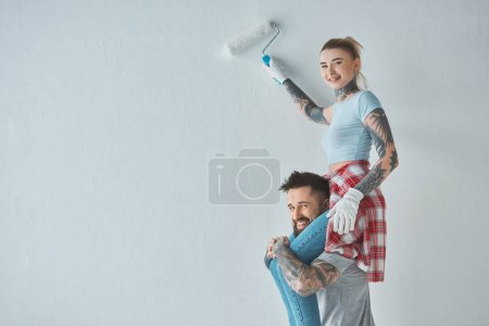 smiling woman with roll paint brush sitting on boyfriends shoulders while painting wall at new home