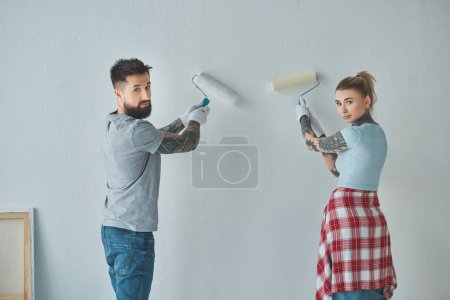 back view of young couple painting wall together at new apartment