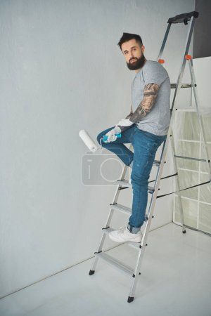 young tattooed repairman with roll paint brush standing on ladder in new apartment
