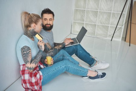 young couple with laptop and credit card shopping online at new apartment