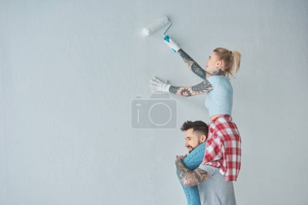 woman with roll paint brush sitting on boyfriends shoulders while painting wall at new home