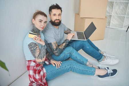 young couple with laptop and credit card looking at camera while shopping online at new apartment
