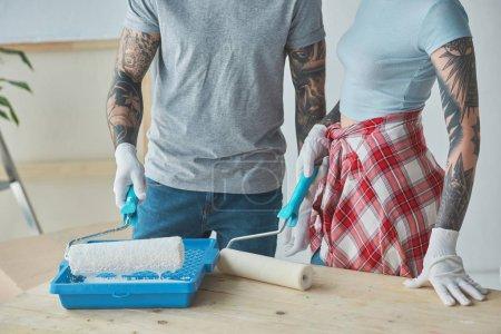 Foto de Tiro cortado de pareja tatuada con rodillo pinceles haciendo reparación casa en Apartamento nuevo - Imagen libre de derechos