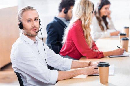 Photo pour Mise au point sélective des opérateurs de centre d'appels travaillant sur les lieux de travail avec le café pour aller au bureau - image libre de droit