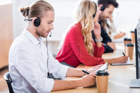 selective focus of call center operators in headsets with notebooks working at workplace in office