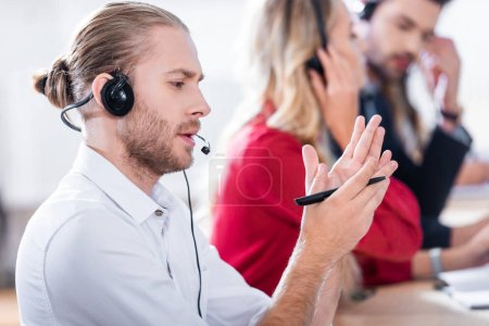 Foto de Enfoque selectivo de los operadores de centros de llamada en auriculares con cuadernos de trabajo en el lugar de trabajo en oficina - Imagen libre de derechos