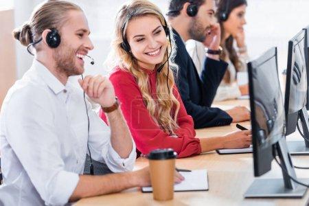 Foto de Enfoque selectivo de sonreír operadores del centro de llamadas trabajando en el lugar de trabajo con el café para ir en la oficina - Imagen libre de derechos