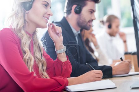 selective focus of call center operators working at workplace in office