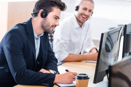 Photo for Selective focus of male call center operators in headsets with notebooks at workplace in office - Royalty Free Image