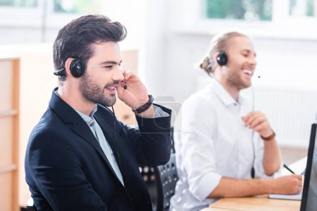 smiling male call center operators in headsets at workplace in office