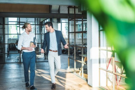 Photo for Smiling business colleagues having conversation while walking in hall - Royalty Free Image