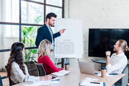 businessman pointing at blank white board during meeting in office