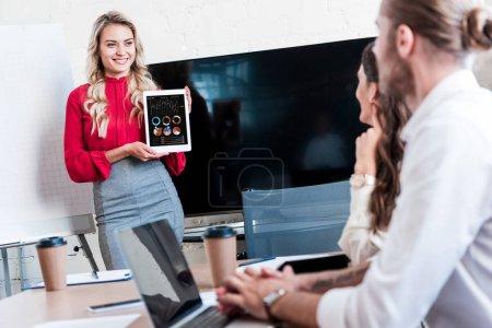 Photo pour Tablette montrant femme d'affaires en main à des collègues au cours de la réunion dans le Bureau - image libre de droit