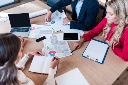 partial view of business team working on new business idea together at workplace with papers in office