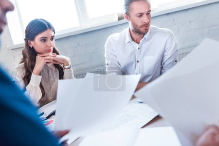 Photo for Partial view of focused businesspeople at workplace with papers in office - Royalty Free Image