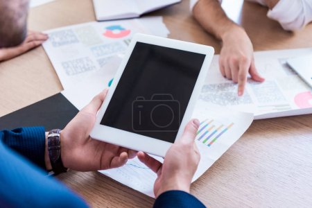 Photo for Partial view of businessman holding tablet with blank screen during meeting in office - Royalty Free Image