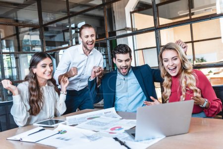 Photo for Happy successful business team looking at laptop screen at workplace in office - Royalty Free Image