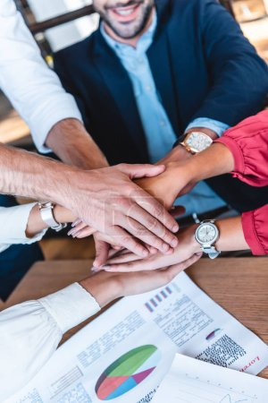 Photo for Cropped shot fo business team holding hands at workplace in office - Royalty Free Image