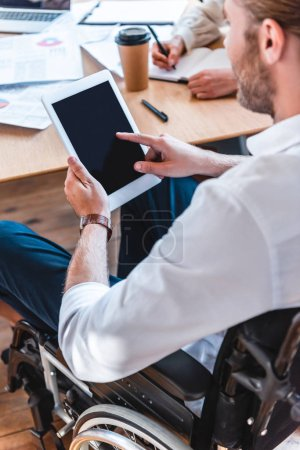 Photo for Partial view of businessman in wheelchair using tablet with blank screen at workplace in office - Royalty Free Image