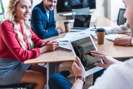 Photo pour Recadrée tir d'homme d'affaires à l'aide de tablette numérique avec réservation de billets pour une application en ligne tout en travaillant avec des collègues de bureau - image libre de droit