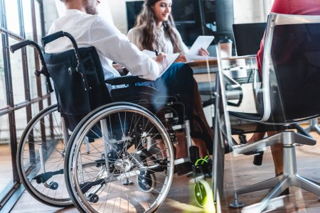 cropped shot of young disabled businessman in wheelchair working with colleagues in office
