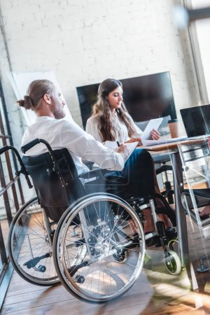 young disabled businessman in wheelchair working with colleague in office