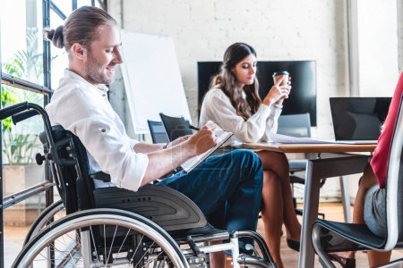 smiling handicapped businessman in wheelchair taking notes at workplace