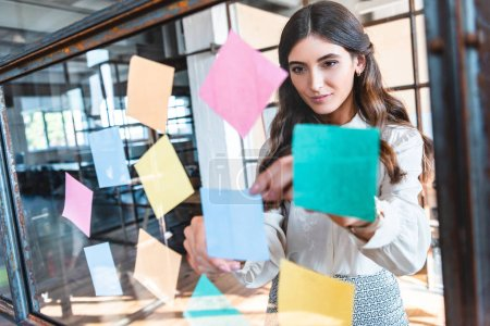 beautiful young businesswoman working with colorful sticky notes in office