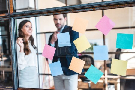 close-up view of colorful sticky notes and smiling business colleagues working behind in office