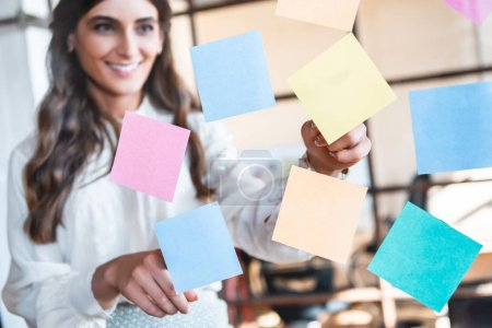 Photo pour Souriante jeune femme d'affaires travaillant avec les notes collantes de bureau - image libre de droit