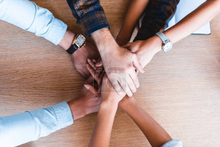partial top view of young business team stacking hands at workplace